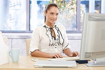 Happy businesswoman busy working on computer