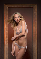 A blond woman posing in erotic lingerie on a frame background