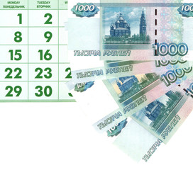 Купюры достоинством 1000 рублей на фоне календаря