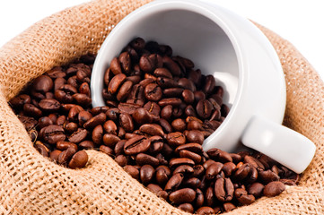 White cup in a bag of coffee beans.