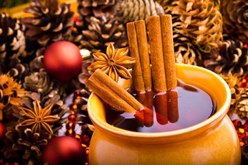 Mulled wine in brown jug with cinnamon and anise