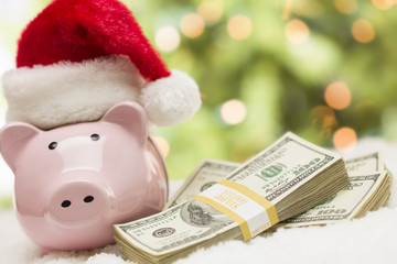 Pink Piggy Bank Wearing Santa Hat Near Stacks of Money on Snowfl