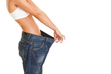woman shows her weight loss by wearing an old jeans, isolated on