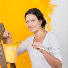 frau streicht ein zimmer gelb