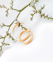 Gold wedding rings and branch flowers