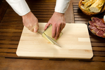 Chef slicing cheese, hands detail