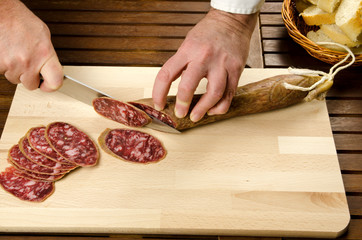 Chef slicing salami, hands detail
