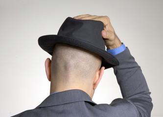 Vista trasera de un hombre colocándose un sombrero.