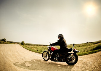 Fototapete - Biker on the road against the sky