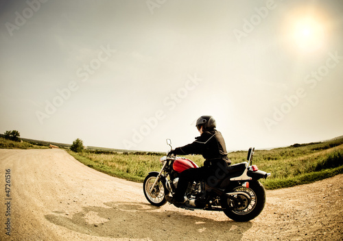 Wall mural Biker on the road against the sky
