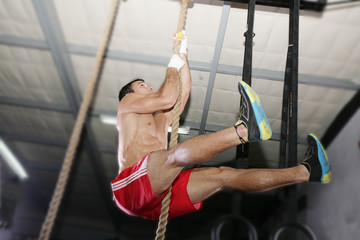 Crossfit rope climb exercise.  Focus in the body.