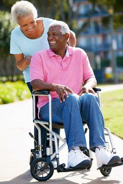 Senior Woman Pushing Husband In Wheelchair
