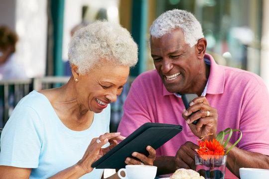 Senior Couple Using Tablet Computer At Outdoor Café