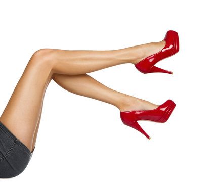 Perfect female legs wearing high heels isolated on white