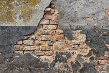 Old damaged wall with bricks and stucco