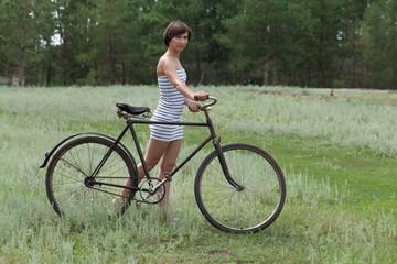 Девушка ведёт по полю старый велос