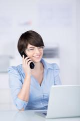 motivierte frau telefoniert im büro