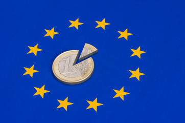 zerteilte Euro Münze auf der EU Flagge