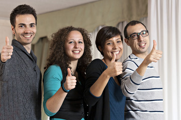 two young couples smile at with thumbs up