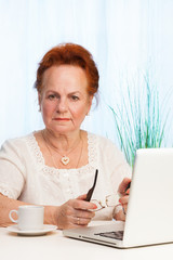 old woman sitting with laptop