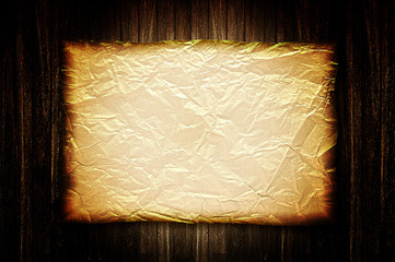 Fototapete - Burnt old crumpled paper on wood background