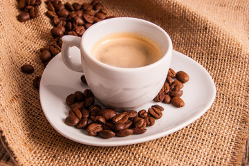 Cup of italian espresso on jute background and coffee beans