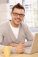 Handsome guy using laptop smiling