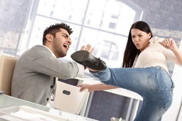 Young woman kicking boyfriend
