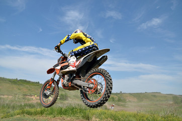 Driver motorcycle MX flies over hill