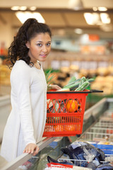 Woman With Shopping Basket Standing At Checkout Counter In Super