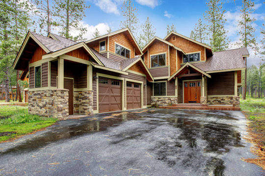 Large mountain cabin house with stone and wet driveway.