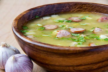 Pea soup with smoked sausages in a wooden plate