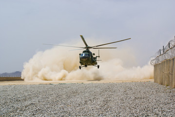 Poster Helicopter helicopter landing in cloud of dust on desert