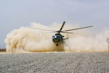 Zelfklevend Fotobehang Helicopter helicopter landing in cloud of dust of desert