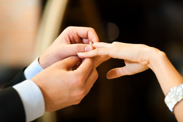 Man gently sticks a diamond ring on the finger of his fiance