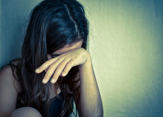 Lonely girl crying with a hand covering her face