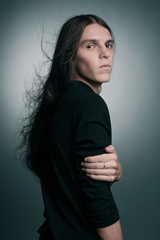 Arty portrait of a fashionable male model with long hair over da