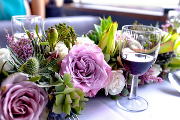Glass of wine placed beside freshly arranged flowers