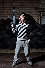 Dangerous young woman with rifle in front of old tires