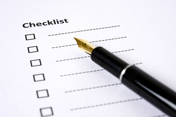 Checklist with a fountain pen on the side on a white background.