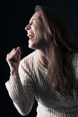 Exultant middle age woman close up portrait on black background.