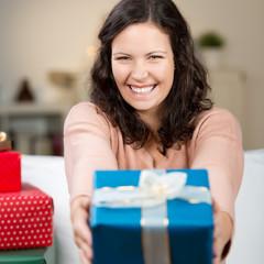 lachende frau überreicht ein weihnachtsgeschenk