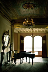 Piano room with yellow walls and many windows