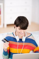 junge frau mit laptop und kreditkarte