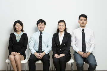 Happy Chinese business team sitting in a row.