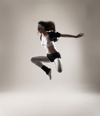 A young and fit Caucasian woman jumping in sporty clothes