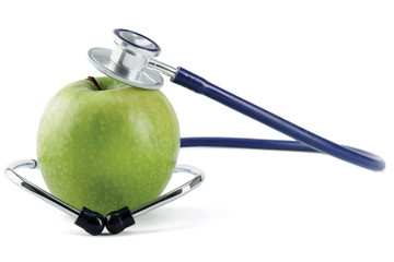 Stethoscope and green apple isolated on white background