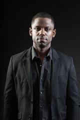 Young black man wearing suit on dark background. Studio shot