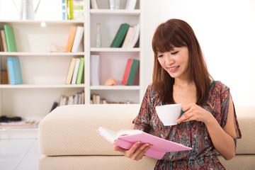 happy asian girl reading on sofa