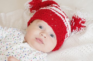 Portrait of the ridiculous baby in a red knitted hat (3 months)